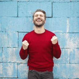 happy man standing in front of a wall