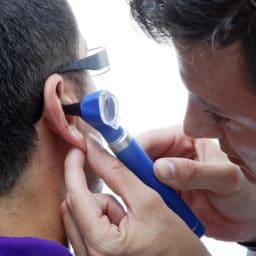 Doctor looking in his patient's ear