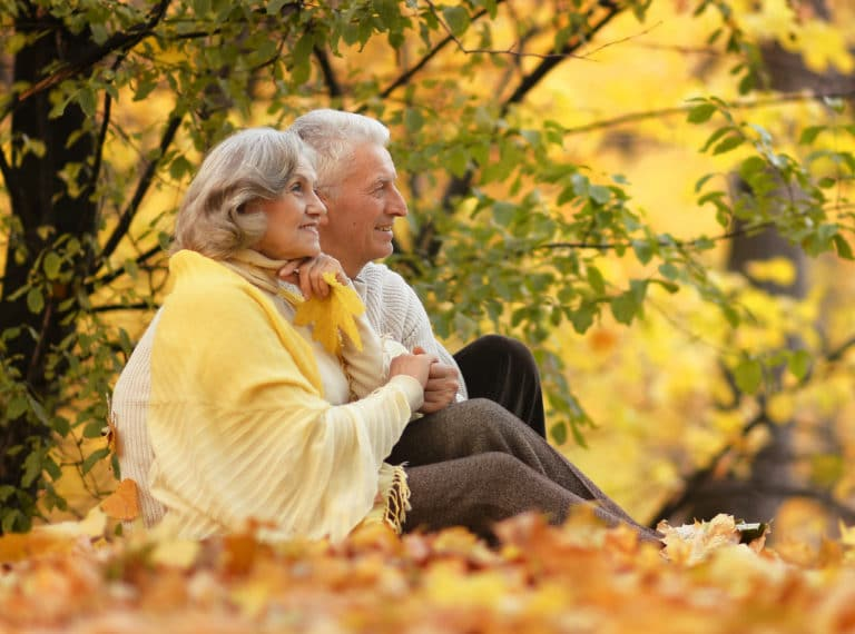 older couple sitting in a park in the fall