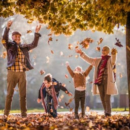 Playful grandparents and their grandkids having fun while throwing autumn leaves in the park
