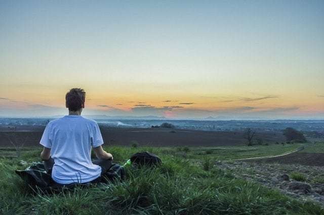 Person meditating on a hill