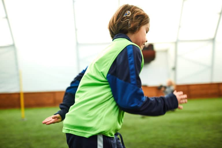 Boy with cochlear implant running on soccer field