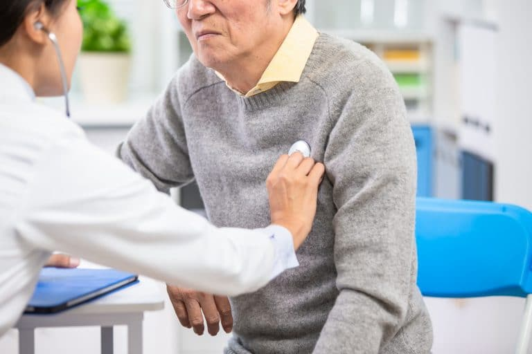 doctor with a stethoscope on a mans chest
