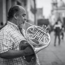 Black and white photo of man playing a French horn