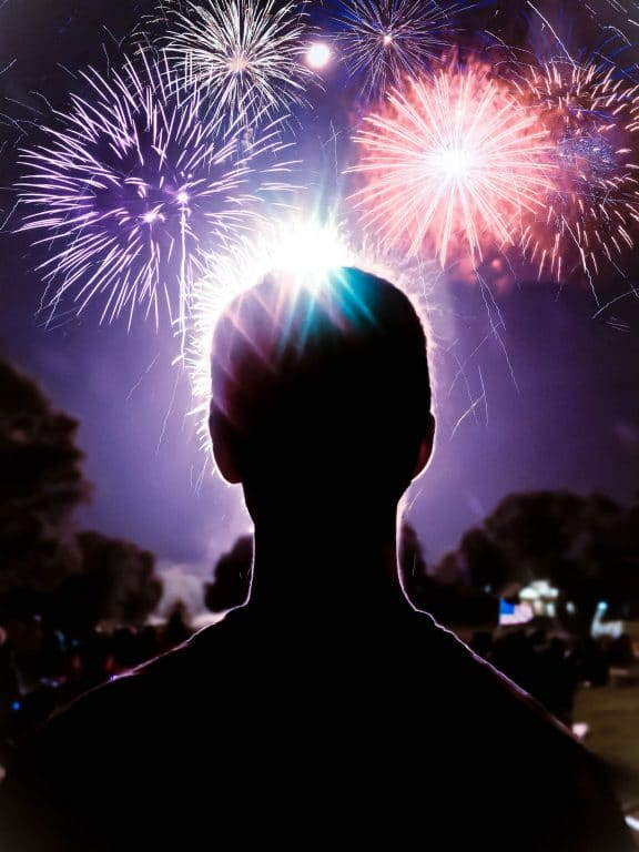 a man looking out at fireworks