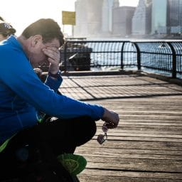 Man sitting on a bench on a pier rubbing his eyes out of exhaustion