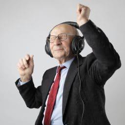 Older man listening to music through headphones and dancing