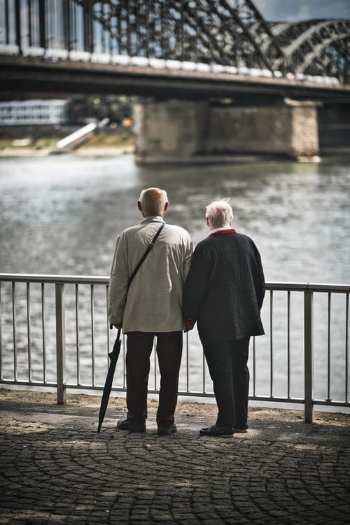 Older couple stands and looks out at waterfront