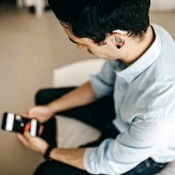 Younger man with a hearing aid using a smartphone.